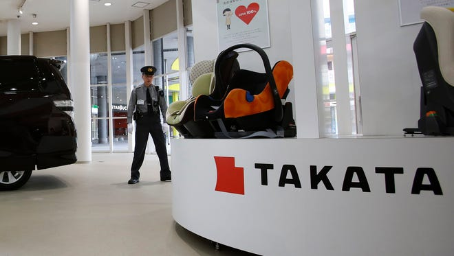 FILE - In this Nov. 6, 2014 file photo, a security guard stands by child seats, manufactured and displayed by Takata Corp. at an automaker's showroom in Tokyo. Japanese automaker Honda Motor Co. expanded its recalls related to defective air bags on Thursday, Nov. 13, 2014,  saying a driver in Malaysia died in an air bag-linked accident earlier this year. The air bags, made by Japanese manufacturer Takata Corp., have faulty inflators that can explode, hurling shrapnel toward drivers and passengers.(AP Photo/Shizuo Kambayashi)