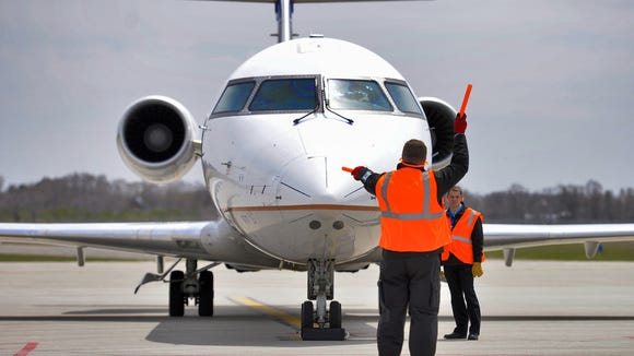 A St. Cloud Regional Airport ground crewman signals for the United Express Canadair CRJ200 to spool up its engines in summer 2014.