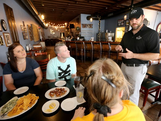 Shawn Hackinson, one of the owner of The Alley on Main, talks to some of his patrons at his restaurant. Dining there for the first time are, clockwise from left, Jenae Jones, Chad Cope, Judy Cope, and not seen Carolyn Hobt.