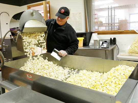 Jeff Faris dumps a batch of popcorn at the company's factory on Industrial Parkway in Fond du Lac.