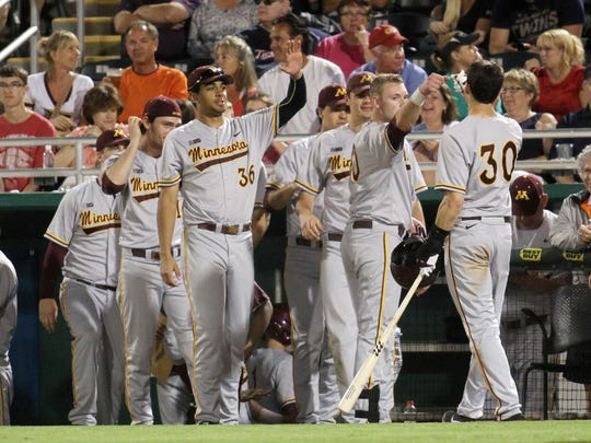 Don Moti, of the University of Minnesota Golden Gophers, is congratulated after scoring the first point against the Minnesota Twins during a game at Hammond Stadium on Wednesday.