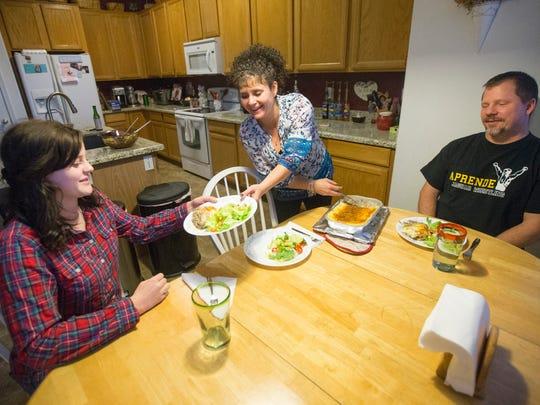 Jenny Beutner serves dinner to her daughter, Kayleigh