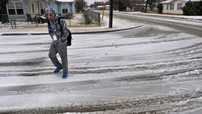 Abilene High School student Trey Robinson walks home from school Wednesday morning, Feb. 21, 2018 after his mother called to release him early. Trey had to walk 1.5 miles to his home off Pine Street because he was told the CityLink bus system had shut down due of the ice storm. He was given a ride the rest of the way by the photographer. Wednesday's ice storm slowed the Big Country to a halt, closing schools and businesses across the region as sleet and freezing rain fell off an on most of the day.