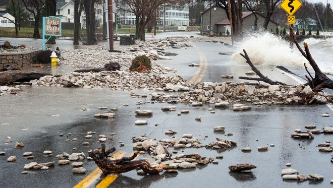 Waves carrying debris crash over East Bayshore Road on the eastern tip of Marblehead during the weekend's strong nor'easter.