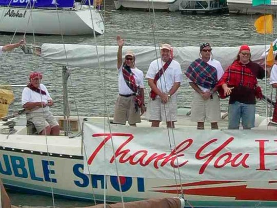 Bob MacIntyre, a 50-year member of Genesee Yacht Club, at the helm of his famed Double Shot sloop during a Rochester Hospice Regatta race he helped found. Around 60 boats take part each year. Mr. MacIntyre died on Nov. 8. He was 86.