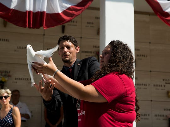 April Ruiz releases a dove in honor of her brother, Marine Austin Ruiz, who died in January during a military training exercise, during a Memorial Day service at the Naples Memorial Gardens at Hodges Funeral Home on Monday, May 29, 2017.