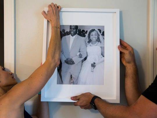 Heather and Andrew Caine hang the wedding photo of Guiseline Fortune-Brumaire and Fritz Brumaire while staging the family's Habitat for Humanity home in Golden Gate Estates on Monday, June 26, 2017. Caine is part of a team of Realtors and designers who donated the furniture and their services to make the house a home, which was revealed to the family on June 29.