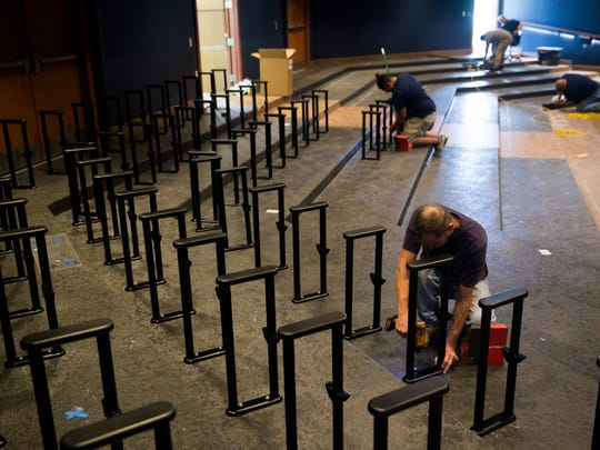 Workers begin to install new seating at the G&L Theater, home of TheatreZone, at the Community School of Naples on Friday, Dec. 15, 2017, in North Naples. In the wake of Hurricane Irma the theater had to have carpet removed, walls repainted and new chairs installed.