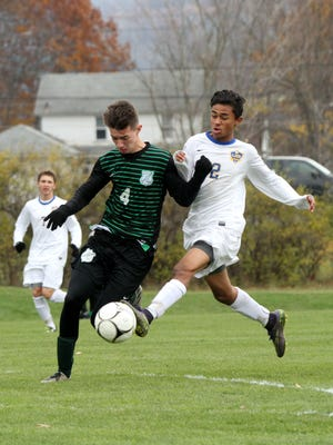 Lansing's Langston Hopkins gets a shot off at the top of the box as Bishop Ludden's Mack McCurn cuts in front of him during Saturday's Class C state quarterfinal at the Wright National Soccer Campus in Oneonta.