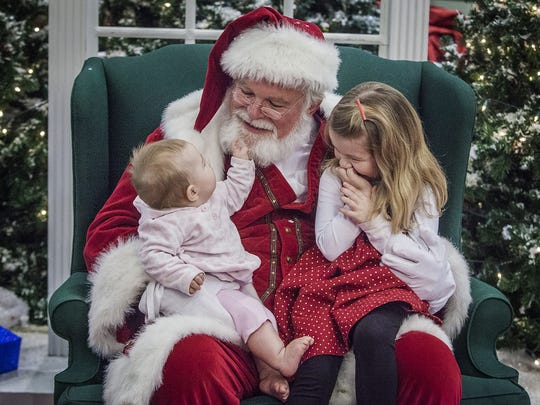 Caitlin Stuttle tests the integrity of Santa's beard while her sister, Evie, waits to tell him what she wants for Christmas at the Muncie Mall in this file photo.