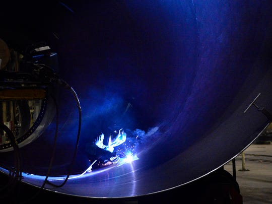 FILE - Welder Jennifer Scheps, 28, is framed inside several cans that she is welding together to create a wind turbine tower section inside the manufacturing plant at Broadwind Towers Inc., located in the City Center industrial park on the Manitowoc River peninsula.
