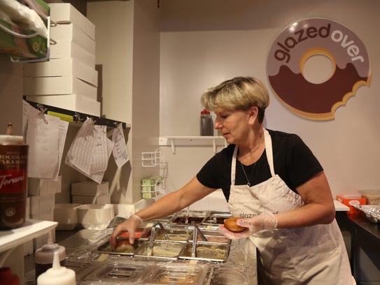 Lisa Tompkins, owner, glazes a doughnut at Glazed Over