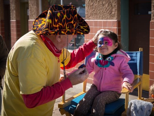 Gracie Warren, 4, enjoys getting her face decorated by a Possum Ranch painter at the Las Cruces Farmers and Crafts Market.
