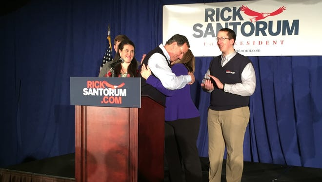 Rick Santorum hugs his wife, Karen, while addressing supporters Monday night at the Hilton Garden Inn in Johnston.