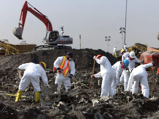 In this Oct. 24, 2001 file photo, New York police officers in biohazard suits painstakingly sift through wreckage of the World Trade Center as it's dumped at the Fresh Kills Landfill on Staten Island in New York. The last barge of regular trash was delivered in 2001 when the site was closed, but the landfill reopened for several months after Sept. 11 when more than 1 million tons of material from the World Trade Center site was screened and sifted there as part of the search for human remains. Today the 2,200-acre site is well on its way to becoming Freshkills Park, the largest landfill-to-park project in the world. (AP Photo/Beth A. Keiser, File)