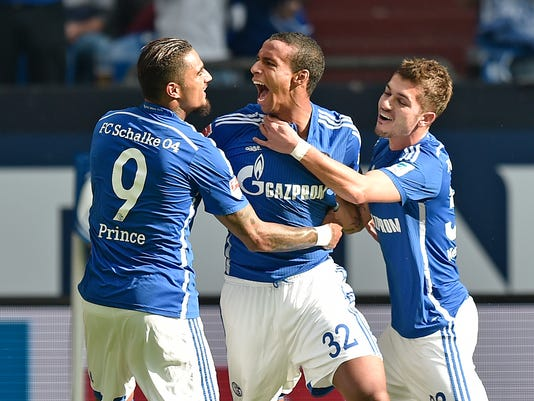 Schalke's Joel Matip from Cameroon, center, celebrates his opening goal with Kevin-Prince Boateng from Ghana, left, and Roman Neustaedter, right, during the German Bundesliga soccer match between FC Schalke 04 and Borussia Dortmund in Gelsenkirchen, Germany, Saturday, Sept. 27, 2014. (AP Photo/Martin Meissner)