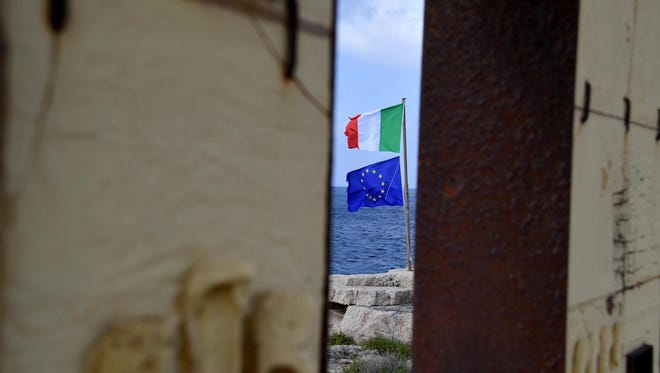 The European and Italian flags fly next to the 'Door of Europe' monument during the European Relationship for Mediterranean Security (ERMES) meeting in Lampedusa, Italy, June 7, 2017.