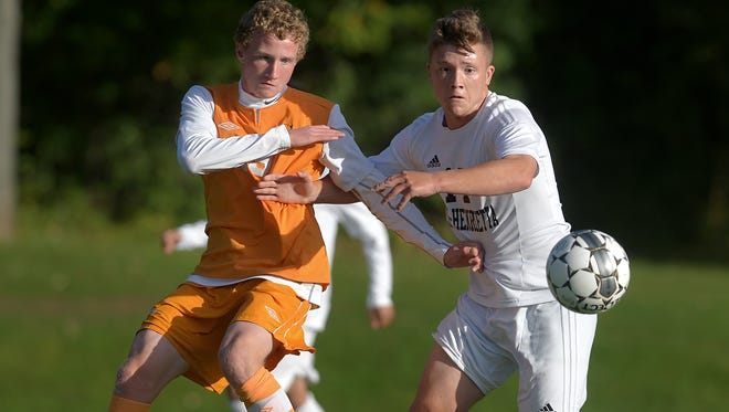 Rush-Henrietta's Griffin Deeter, right, and Churchville Chili's Riley Baker fight for position on the ball during a regular season game played at Rush-Henrietta High School on Thursday, Oct. 1, 2015. Churchville beat R-H 2-1.