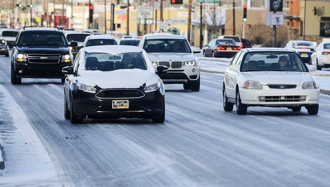 Traffic creeps along on an ice coated Lomas Blvd. as a winter storm brought more ice than snow to Albuquerque, New Mexico. Friday, Jan. 6, 2017.