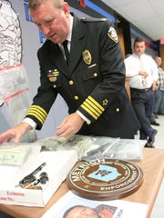 Marion Police Chief Bill Collins arranges bags of cash,