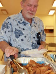 Jack Vermie grabs a piece of fish during the Fish Fry at Mitchellville Community Center.