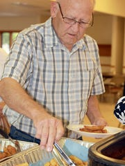 Jim Appleget grabs a collection of fries at the Mitchellville Fish Fry on Friday.