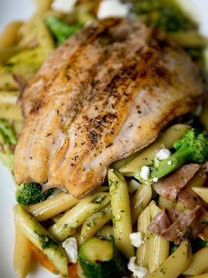 Rainbow trout on a bed of vegetables and noodles made by sous chef Mike Piltz at Father Fats, Monday, August 17, 2015.