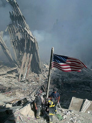 Three New York City firefighters raise the American flag amid the rubble of the World Trade Center, Tuesday, Sept. 11, 2001.