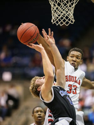 Houlka's Madarius Hobson (33) blocks the shot of Sacred Heart's  William Agnew (14). Houlka and Sacred Heart played in the MHSAA Boys Class 1A basketball on Thursday.