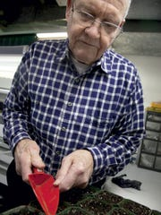 York County Master Gardener Burt Kniseley sows seeds in the basement of his Spring Garden Township home in this 2013 photo.
