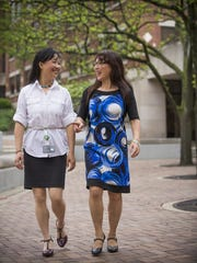 Jirong Lu (left) and Ling Liu chat outside at Eli Lilly and Co. in Indianapolis on April 21, 2016.