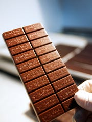 Evan Ackerman, a chocolate maker at French Broad Chocolates, holds a chocolate bar just taken from a mold.