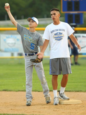Big brother Joseph Mancini helps out at practice as a base runner with Michael Mancini playing short.