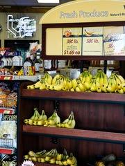 Fresh bananas, potatoes and onions sit on the self