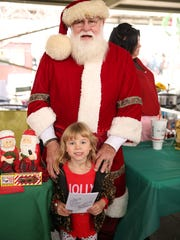Santa poses with Adele Griffin, 4, at Jackson's Christmas in the City Saturday at the farmer's market downtown.