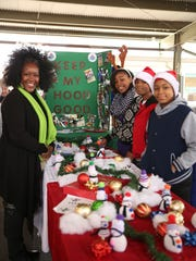 Keep My Hood Good offered ornaments for sale Saturday during Jackson's Christmas in the City held downtown at the farmer's market.  On the left is Juanita Jones, on the right from front to back, Kenneth Rogers, Kaden Rogers, and Jenesis Rogers.