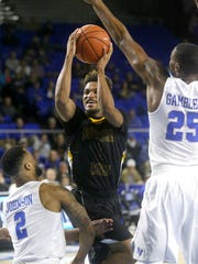 Southern Miss' Cortez Edwards (1) goes up for a shot as he is covered by MTSU's Antwain Johnson (2) and Karl Gamble (25) during their game Thursday.