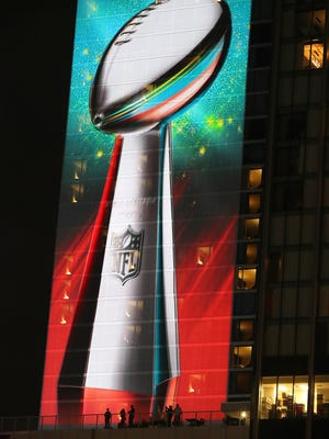 Fans on a hotel balcony look up at a giant image of the Lombardi Trophy overlooking Super Bowl Live at Discovery Green park on Thursday, Feb. 2, 2017, in Houston.