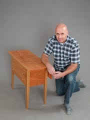 Kevin Deraps kneels by a table he made at Vermont Woodworking School's Johnson State College degree program.
