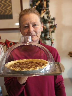 Marty Davis, owner of Sweet 103 Bakery, holds a pecan pie destined for a take-and-bake customer.