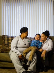 Tanarra Gray, 26, left, and Jazmyne Reich, 23, right, pose for a photo with Elijah Gray, 4, center, at their home on Friday, Dec. 22, 2017, in Des Moines. Elijah was left in Gray's possession by his biological mother who didn't want him, but due to procedural issues in the court system, Gray hasn't been able to adopt him.