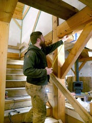 Brad Simpson shows support beams in his parents' home in Indianola. The building project aims to utilize local materials and the expertise of local carpenters and builders.