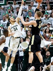 Michigan State's Gavin Schilling, left, guards Purdue's