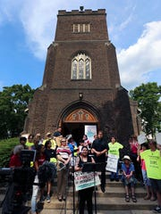 Activists stage a green-card rally June 8, 2018, on the steps of the Reformed Church of Highland Park, New Jersey, to highlight the case of Cloyd Edralin, a father of four with an 11-year-old firearm conviction who had been arrested four days earlier.