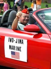 World War II veteran Marcel Bisson waves to the crowd