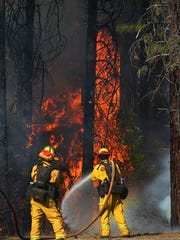 Firefighters monitor fire movement as it crosses Highway