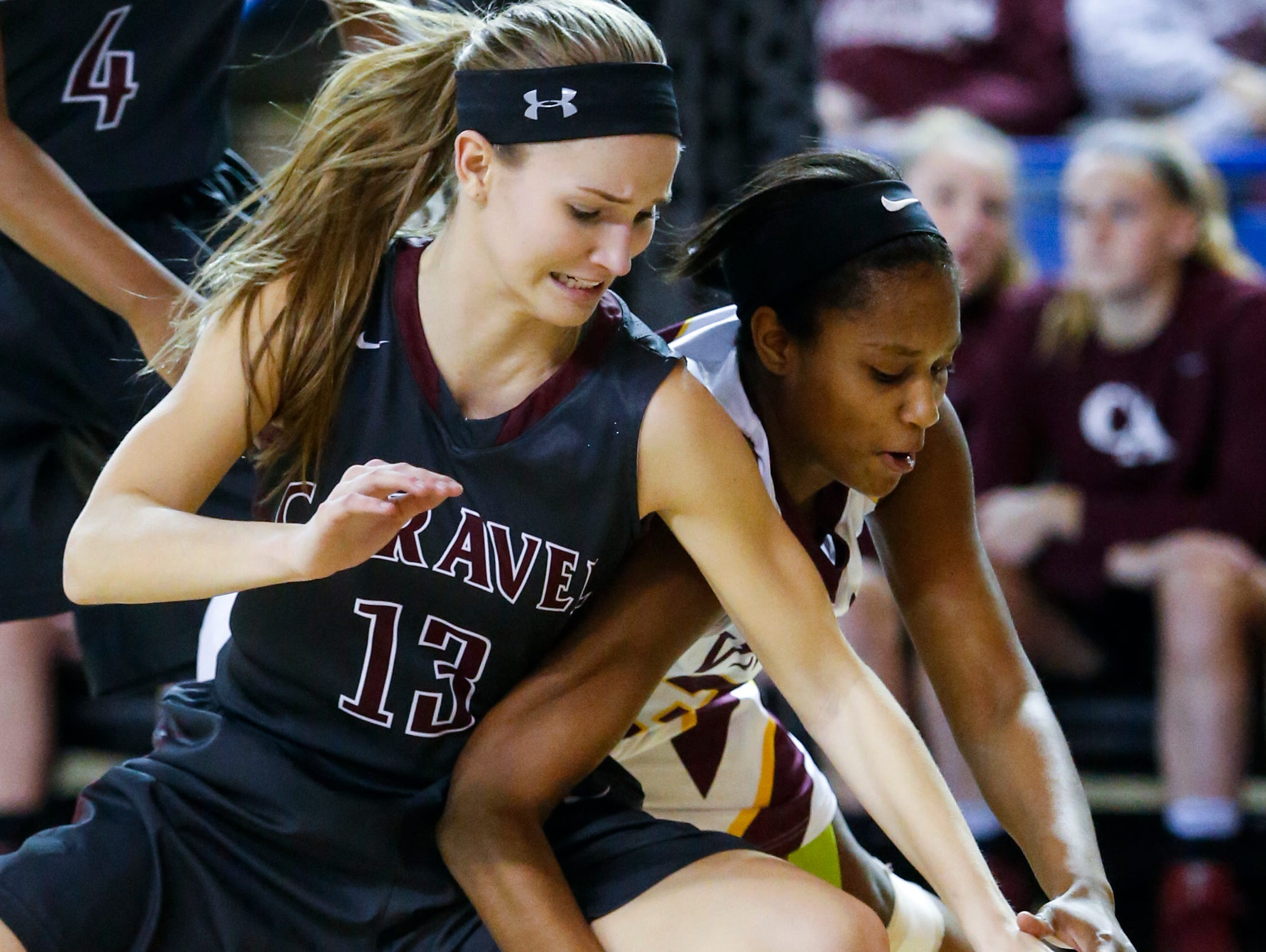 Caravel's Grace Lange (left) clashes with St. Elizabeth's Alanna Speaks for a loose ball in the first half of a DIAA state tournament semifinal Wednesday at the Bob Carpenter Center.
