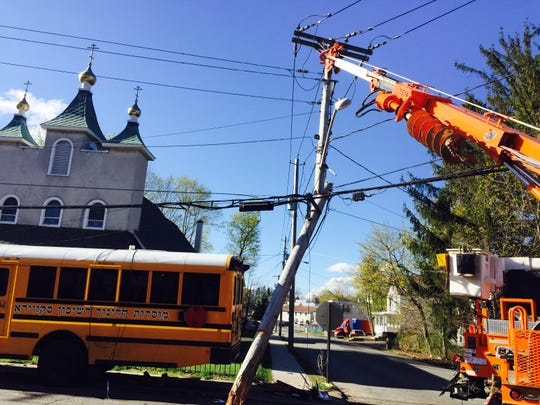 An Orange and Rockland Utilities Inc. truck lifts a snapped pole at Church and West streets in Spring Valley. A Yeshiva Avir Yakov bus, right, ran a stop sign at West and Church streets in Spring Valley and crashed into mini bus for East Ramapo School District. The mini bus was pushed about 40 feet into a utility pole. The pole cracked as the smaller bus went into a church's iron fence. The East Ramapo driver complained of body pain and was taken to Nyack Hospital by Spring Hill Ambulance Corps.