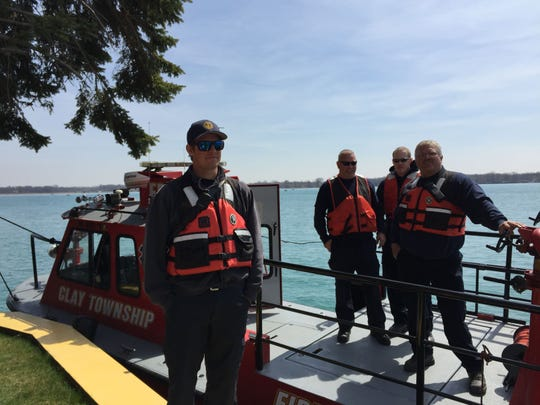 Members of the Clay Township Fire Department stand near the St. Clair River where divers work to recover a Border Patrol vehicle Wednesday, April 29, 2015.