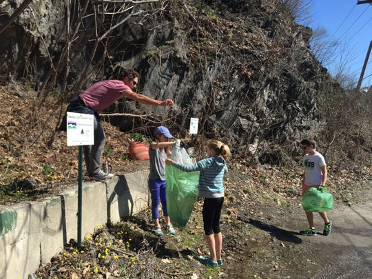 Louisa Braun, 11, left in hat, and Phoebe Gingold, 10, help fill a green garbage bag with litter for Green Up Day in Montpelier. The group spent much of the morning in a parking lot on Elm Street.